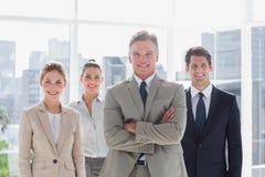 Werkgever met zijn gevouwen wapens status met glimlachende collega's behin stock foto's