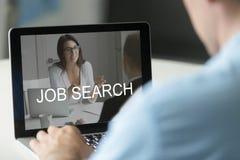 Werkloze man die laptop met behulp van die online het werk zoeken, van toepassing zijnd voor stock fotografie