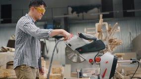 Werkman in beschermende brillen die luchtcompressor met behulp van om zaagsel van cirkelzaag te blazen stock footage
