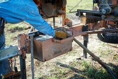 Werkman bij een zaagmolen die een malenmachine aanpassen royalty-vrije stock afbeeldingen