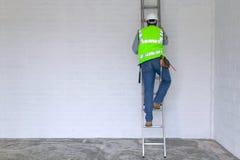 Werkman die een ladder beklimt Stock Foto's