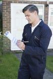 Werkman die Raming voor het Werk aangaande Huisbuitenkant voorbereiden Stock Foto