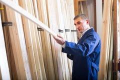Werkman die zich met houten plank bevinden Royalty-vrije Stock Afbeelding