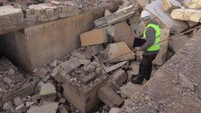 Werknemer bij beschadigde huisruïnes stock footage