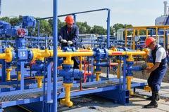 Werknemer die aan de installatie van de gasbehandeling werken Stock Foto