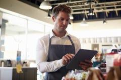 Werknemer die in Delicatessen Voorraad met Digitale Tablet controleren royalty-vrije stock foto
