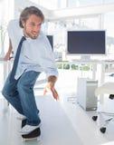 Werknemer die door het bureau schaatsen Stock Afbeelding