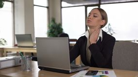 Werknemer die hals aan pijn lijden terwijl het werken aan laptop, zware dag in bureau stock videobeelden