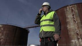 Werknemer op walkie-talkie dichtbij tanks stock footage