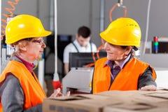 Werknemers die bij productiegebied bespreken royalty-vrije stock foto's