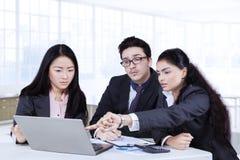 Werknemers die businessplan in bureau bespreken Stock Afbeeldingen