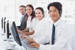 Werknemers die op hun computers typen Stock Afbeelding