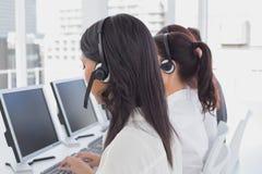 Werknemers die op hun computers typen Stock Foto's