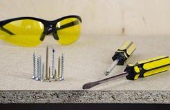 Werkplaats, gele schroevedraaier twee en glazen op een houten lijst royalty-vrije stock foto