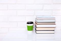Werkplaats met kop koffie en boeken dichtbij bakstenen muur op witte lijst Exemplaar ruimte en selectieve nadruk Stock Afbeelding