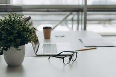 Werkplaats met notitieboekjelaptop Comfortabele het werklijst in van de bureauvensters en stad mening stock afbeeldingen