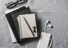 Werkplaats met zaken, onderwijstoebehoren Tablet, telefoon, hoofdtelefoons, blocnote, pen, glazen op grijze achtergrond, hoogste  stock afbeeldingen