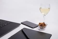 Werkplaats met zwarte laptop computer, digitale grafische tablet en pen, slimme telefoon, droge druiven en glas witte wijn op wit Stock Foto