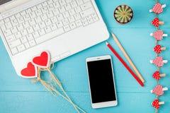 Werkplaats op een blauwe laptop achtergrond, een smartphone en rode decoratieve harten, potloden Valentine-dag, vakantieachtergro royalty-vrije stock fotografie