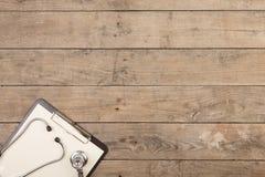 Werkplaats van een arts Stethoscoop en klembord op houten bureau royalty-vrije stock afbeelding