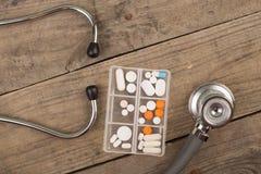 Werkplaats van een arts Stethoscoop, noodsituatieuitrusting, en ander materiaal op houten bureau stock afbeeldingen