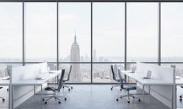 Werkplaatsen in een helder modern open plekbureau Witte die lijsten met moderne laptops en zwarte stoelen worden uitgerust New Yo Royalty-vrije Stock Afbeelding