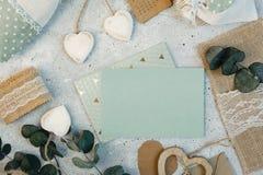 werkruimte De kaarten van de huwelijksuitnodiging, ambachtenveloppen, roze en rode rozen en groene bladeren op witte achtergrond Royalty-vrije Stock Foto