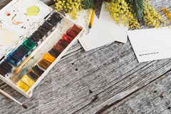 werkruimte Kroonkader met mimosa's, waterverf, penseel en uitstekende prentbriefkaar op houten achtergrond Stock Foto's