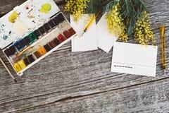 werkruimte Kroonkader met mimosa's, waterverf, penseel en uitstekende prentbriefkaar op houten achtergrond Royalty-vrije Stock Foto