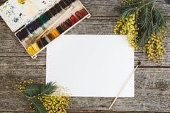werkruimte Kroonkader met mimosa's, waterverf, penseel en uitstekende prentbriefkaar op houten achtergrond Royalty-vrije Stock Fotografie