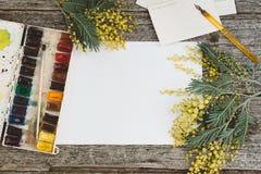 werkruimte Kroonkader met mimosa's, waterverf, penseel en uitstekende prentbriefkaar op houten achtergrond Stock Fotografie