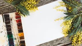 werkruimte Kroonkader met mimosa's, waterverf, penseel en uitstekende prentbriefkaar op houten achtergrond Royalty-vrije Stock Afbeelding
