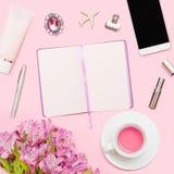Werkruimte met agenda, pen, smartphone, lippenstift, alstroemerias, theekop, schoonheidsmiddelenbuis op pastelkleur roze achtergr royalty-vrije stock fotografie