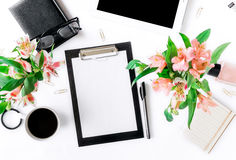 Werkruimte met klembord, bureautoebehoren, koffie en boeket royalty-vrije stock afbeelding