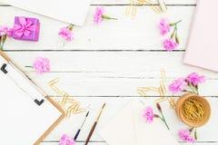 Werkruimte met klembord, notitieboekje, roze bloemen en toebehoren op rustieke lijst De werkruimte van de schoonheidsblog Vlak le Royalty-vrije Stock Afbeeldingen
