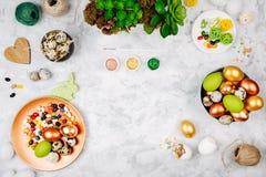 Werkruimte met Pasen-decoratie Geschilderde eieren in dienbladen, suikergoed, bloemen met exemplaarruimte De achtergrond van de v stock fotografie