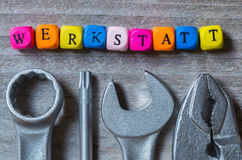Werkstatt in german Workshop letter cube and tool on gray wood stock images