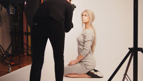 Werkstattbühne hinter dem vorhang - das blonde hübsche Mädchen, das für Fotografen aufwirft - Modell sitzt an den Knien Lizenzfreies Stockfoto