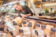 Werkstattschreiberfrau, die Käse in der Supermarktanzeige sortiert lizenzfreie stockfotografie