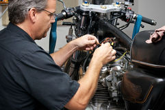 Werktuigkundige die aan antieke motorfiets werken royalty-vrije stock foto's