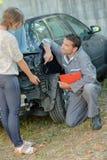 Werktuigkundige die aan schade op achterauto richten royalty-vrije stock afbeelding