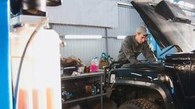 Werktuigkundige die in automobiele garage kap van de auto controleren, brede hoek Stock Afbeelding