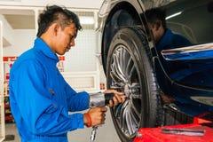 Werktuigkundige die of autowiel schroeven losschroeven bij de garage van de autodienst Stock Foto's