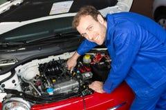 Werktuigkundige die een auto in een workshop of een garage herstellen Stock Foto