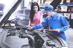 Werktuigkundige die een klant helpen die een auto bevestigen Royalty-vrije Stock Afbeelding