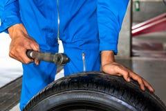 Werktuigkundige die een moersleutel en autowiel in de dienst van de autogarage houden Royalty-vrije Stock Afbeelding
