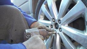 Werktuigkundige die een wiel opzetten en wielnoten op een vehilce in de autodienst aanhalen stock video