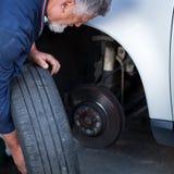 Werktuigkundige die een wiel van een moderne auto verandert royalty-vrije stock afbeelding