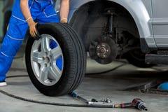 Werktuigkundige die een wiel van een moderne auto verandert Stock Foto