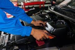 Werktuigkundige die en een gebroken auto in de garage van de autodienst controleren bevestigen Stock Afbeelding